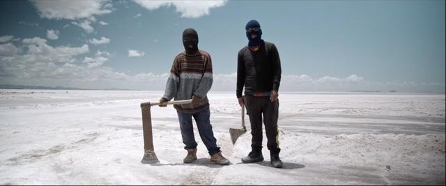 Nico and his co-worker holding axe at Uyuni Salt Flats in bolivia
